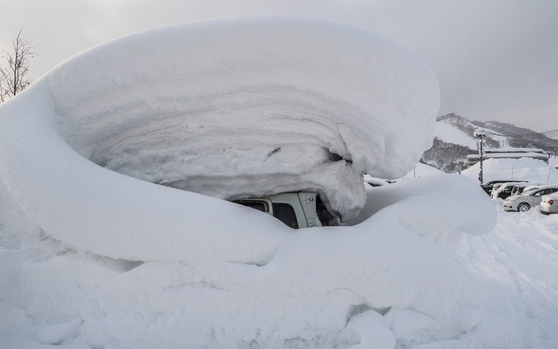 a buried car in a snowy niseko parking lot