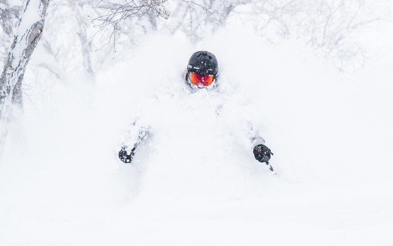 A skier plows through that famous niseko bottomless powder