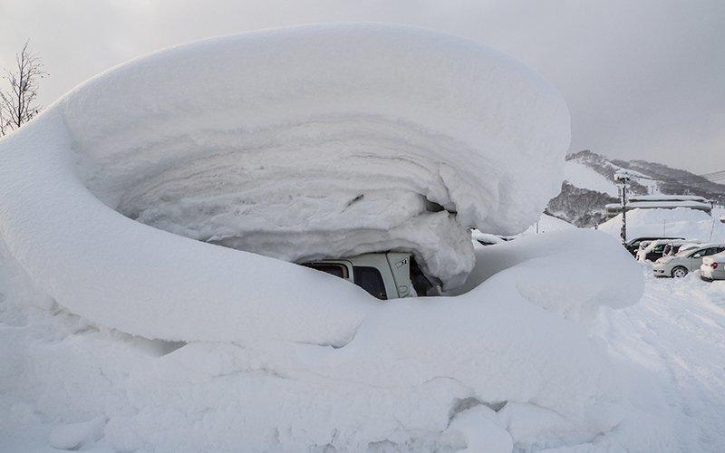 car buried deep in niseko snow